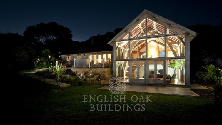 Green Oak Frame House, and glass wall, Cornwall, at night
