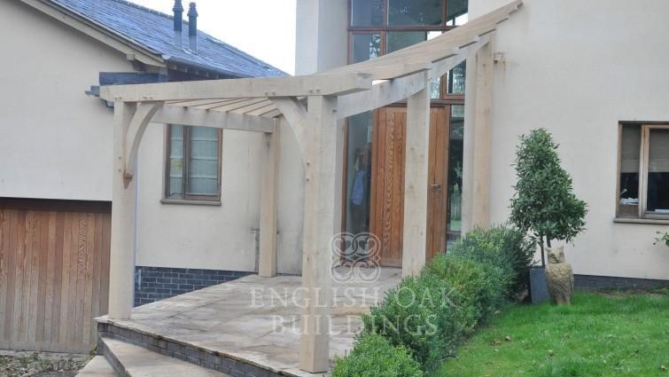 Oak framed entrance pergola with a compound twist design