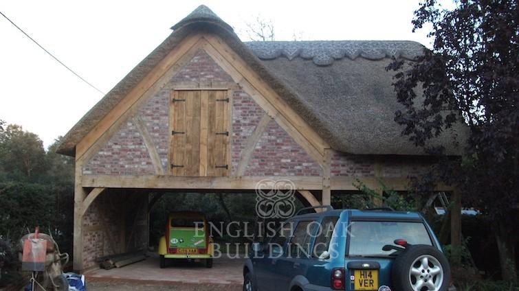 Oak-garage-with-thatch-roof-and-brick-infil-755x424
